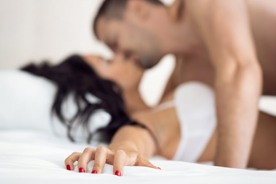 Couple having sex, female hand grabbing sheet