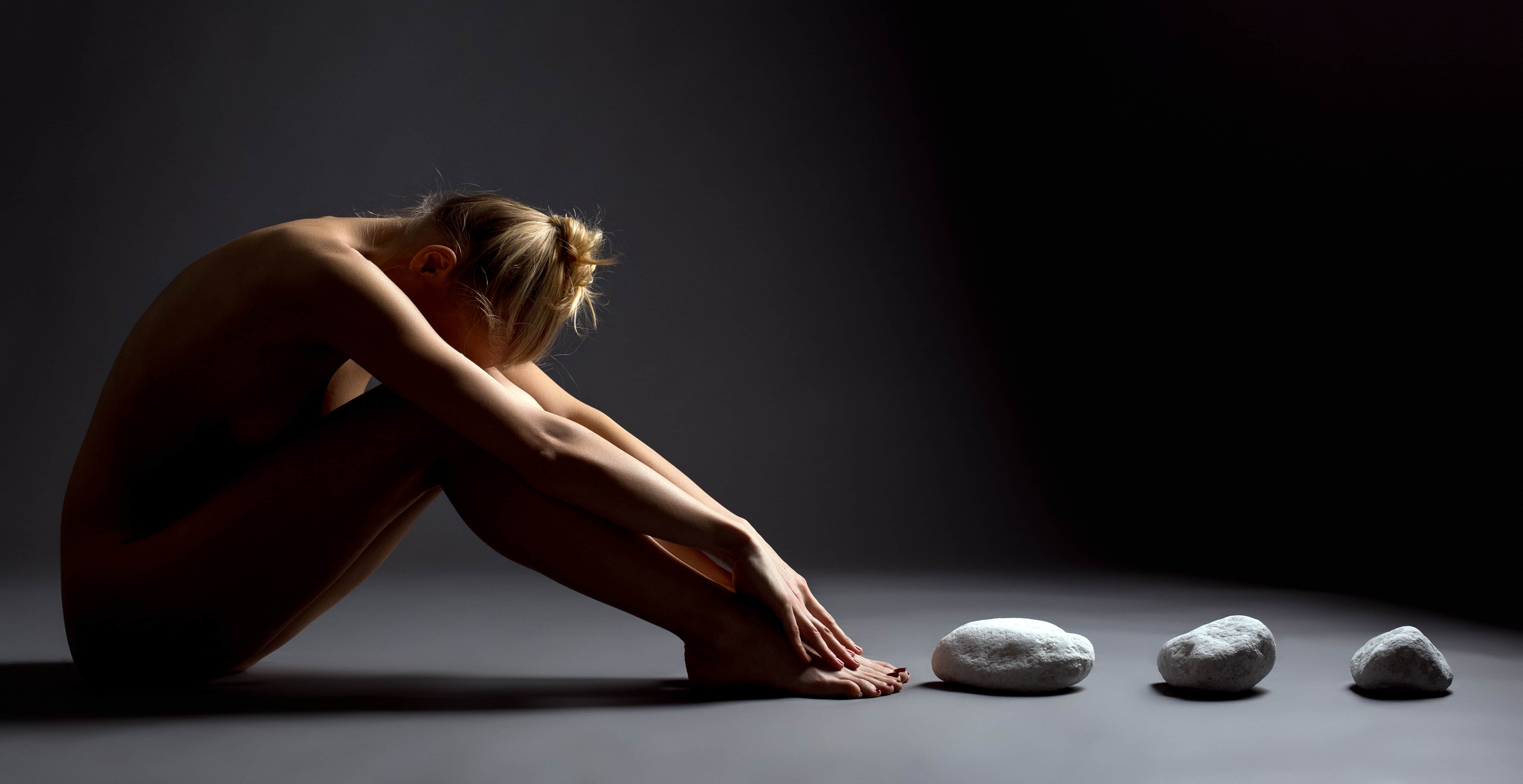 Shot of nude female telekinetic posing with stones