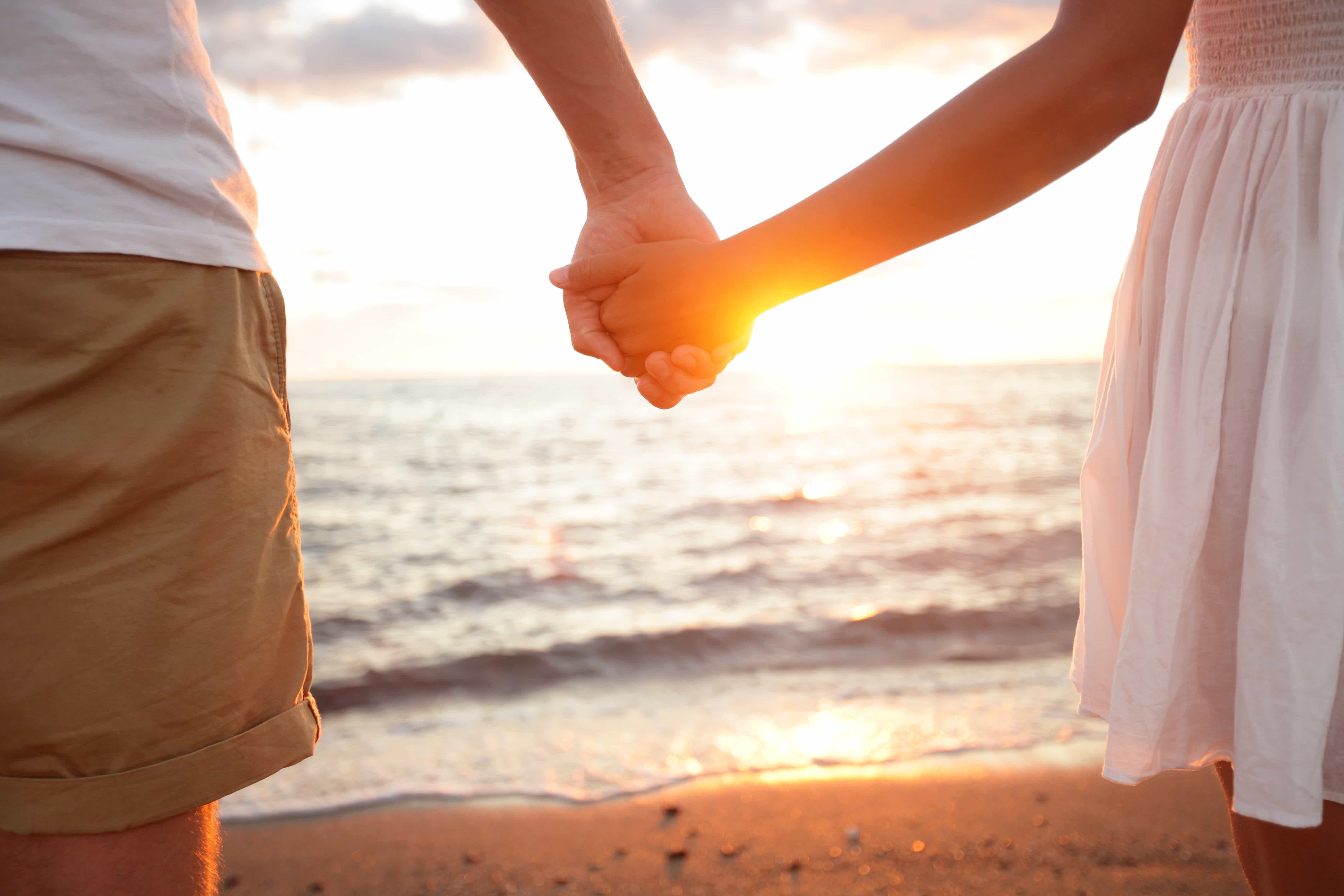 Summer couple holding hands at sunset on beach. Romantic young c