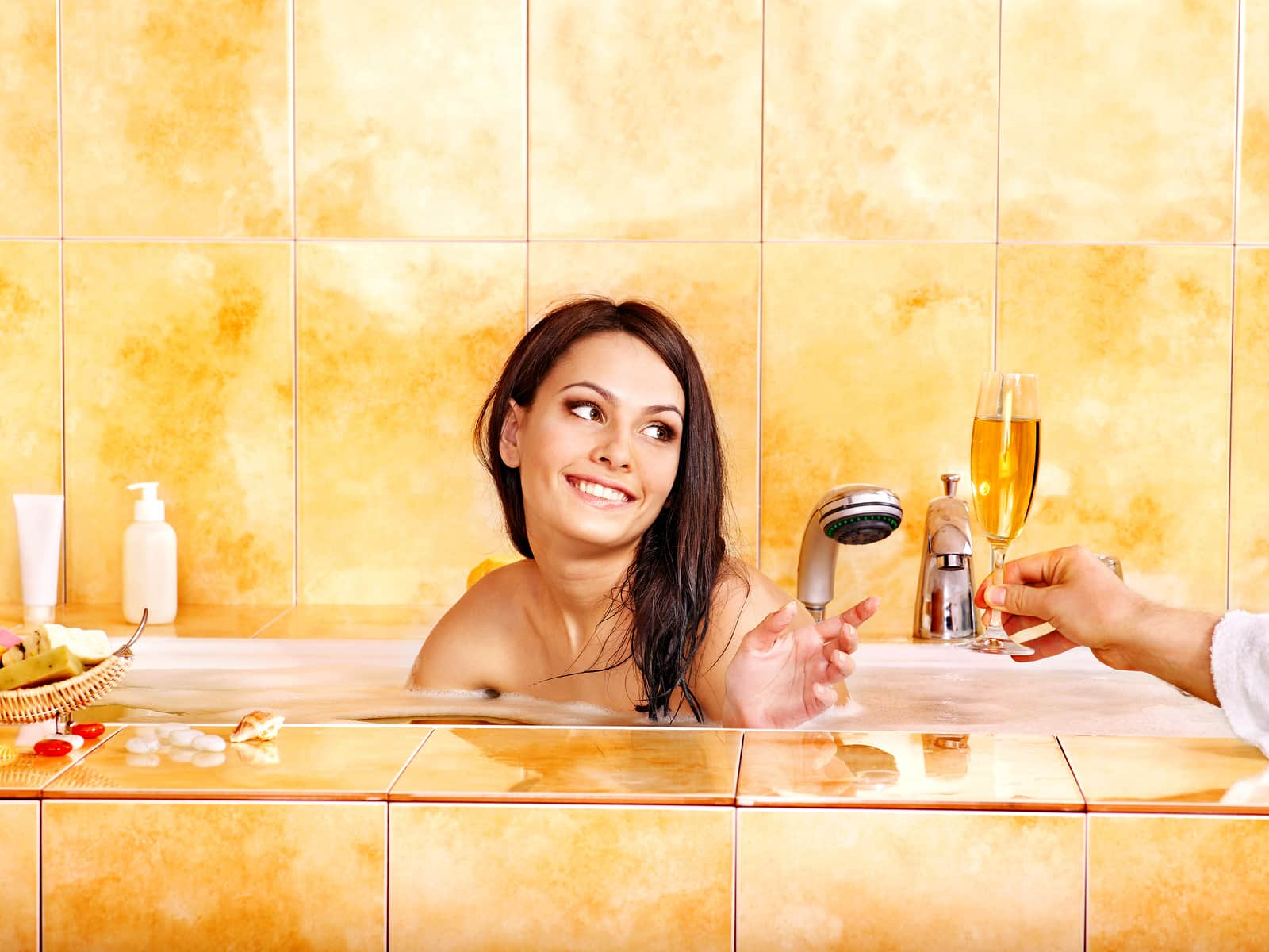 Couple drinking champagne in bathtub.