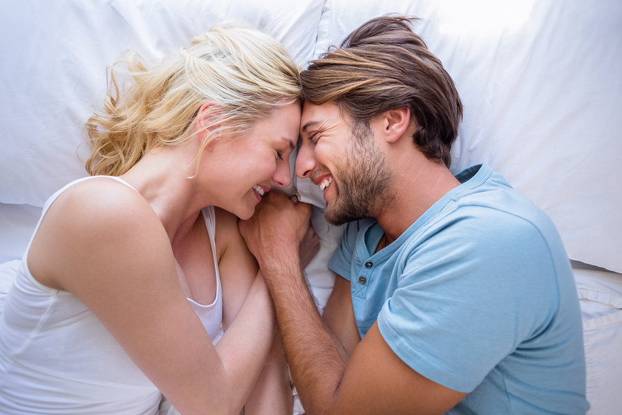 Cute couple relaxing on bed smiling at each other at home in the