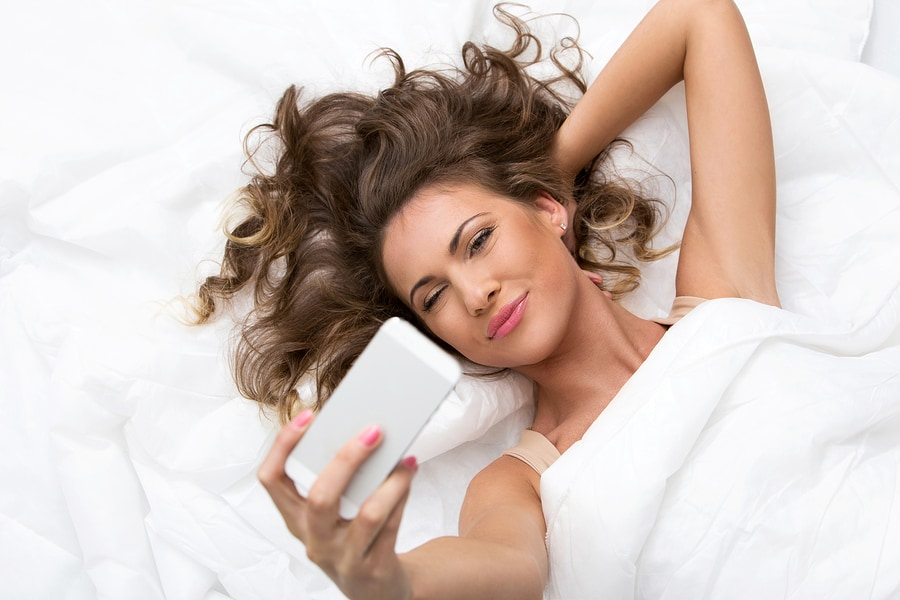 Morning. Cute woman in the bed with mobile phone