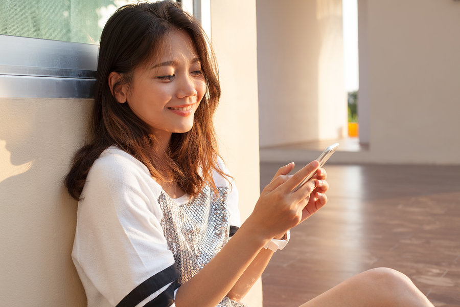 Portrait Of Beautiful Young And Teen Woman Looking To Mobile Pho