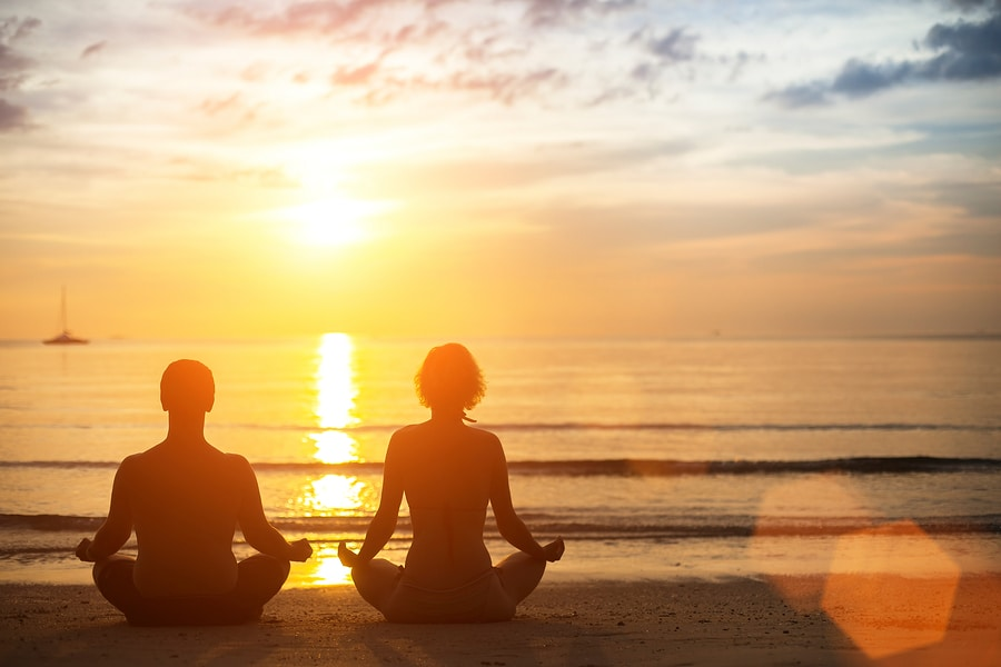Young yoga couple meditating during amazing sunset on the ocean