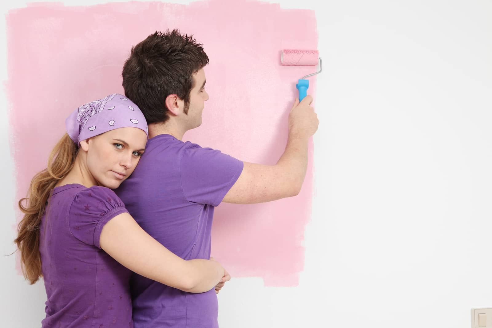 young couple painting baby nursery in new home pink
