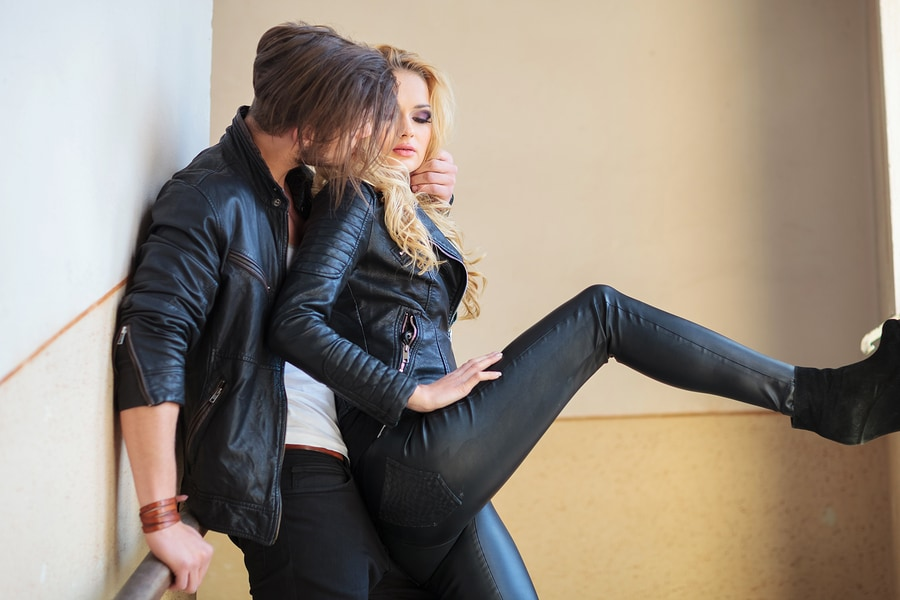 young man in leather jacket is whispering something to his lover