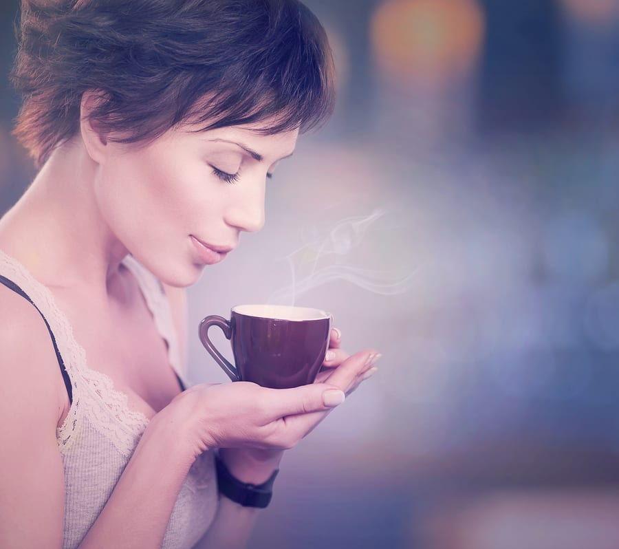 Beautiful Girl Drinking Tea or Coffee. Beauty Woman with Cup of