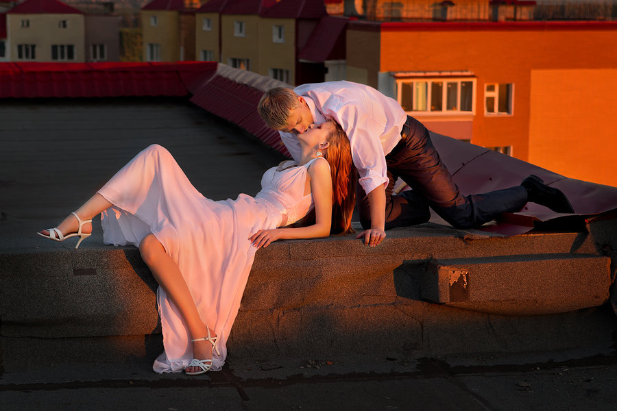 The newly married couple lying on the roof of house in red sunse