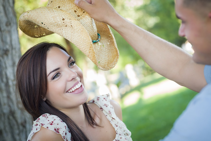Happy Mixed Race Romantic Couple with Cowboy Hat Flirting in the