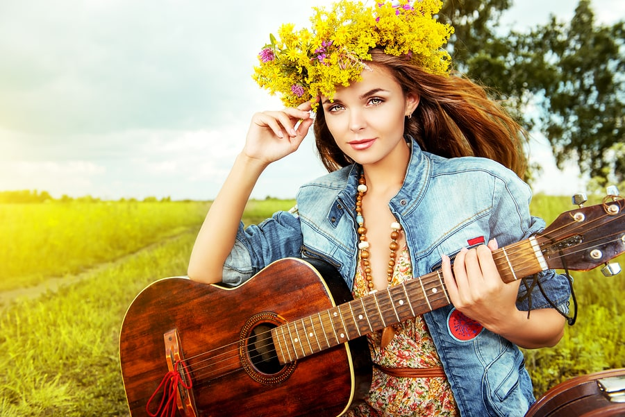 Romantic girl in a wreath of wild flowers playing her guitar. Su