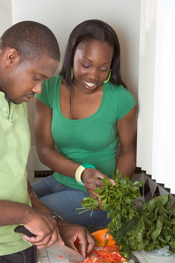 Young Ethnic Couple On Kitchen Slicing Vegetables