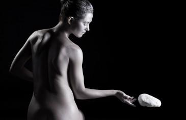 Spiritual nude woman telekinetically moving stone