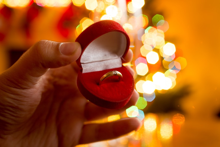 Man Presenting Golden Ring In Box Against Decorated Christmas Tr