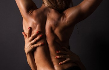 topless Women from behind is hugging by another women with red fingernails.Picture with side light.