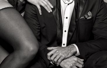 Rich man with lover in underwear posing on sofa closeup black and white