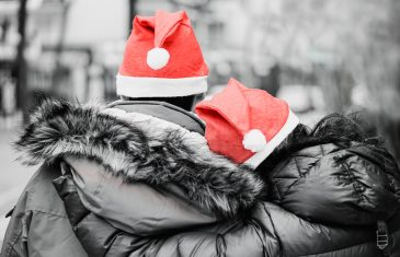 Couple of lovers with red santa's hats on a monochromatic background - Young people having tender moments on christmas time - Holidays concept - Soft focus on left top hat - Color in black and white
