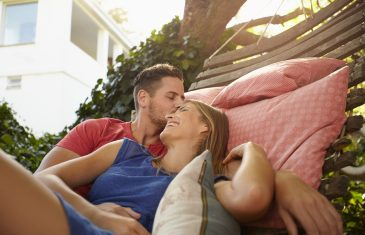 Young couple is cuddling on a hammock. Young man kissing forehead of his girlfriend smiling. Romantic couple outdoors relaxing on a hammock.