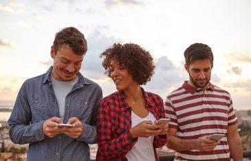 Two guys and a girl looking at their cellphones with happy smiles while wearing casual clothing and bright white natural background