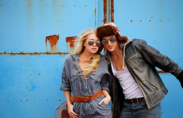 Attractive adventurous couple, with blue grunge metal wall background