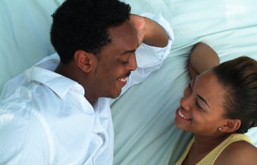 young couple talking on bed laughing and smiling