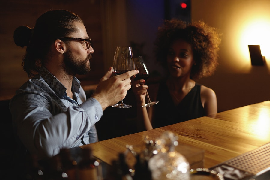 Fashionable interracial couple drinking wine during date sitting at restaurant having romantic evening and nice conversation raising glasses to love at first sight. Hipster man proposing toast