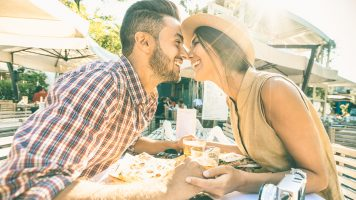 Couple in love kissing at bar eating local delicacie on travel excursion – Young happy tourists enjoying moment at street food restaurant – Relationship concept with lovers at first date