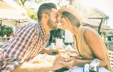Couple in love kissing at bar eating local delicacie on travel excursion - Young happy tourists enjoying moment at street food restaurant - Relationship concept with lovers at first date